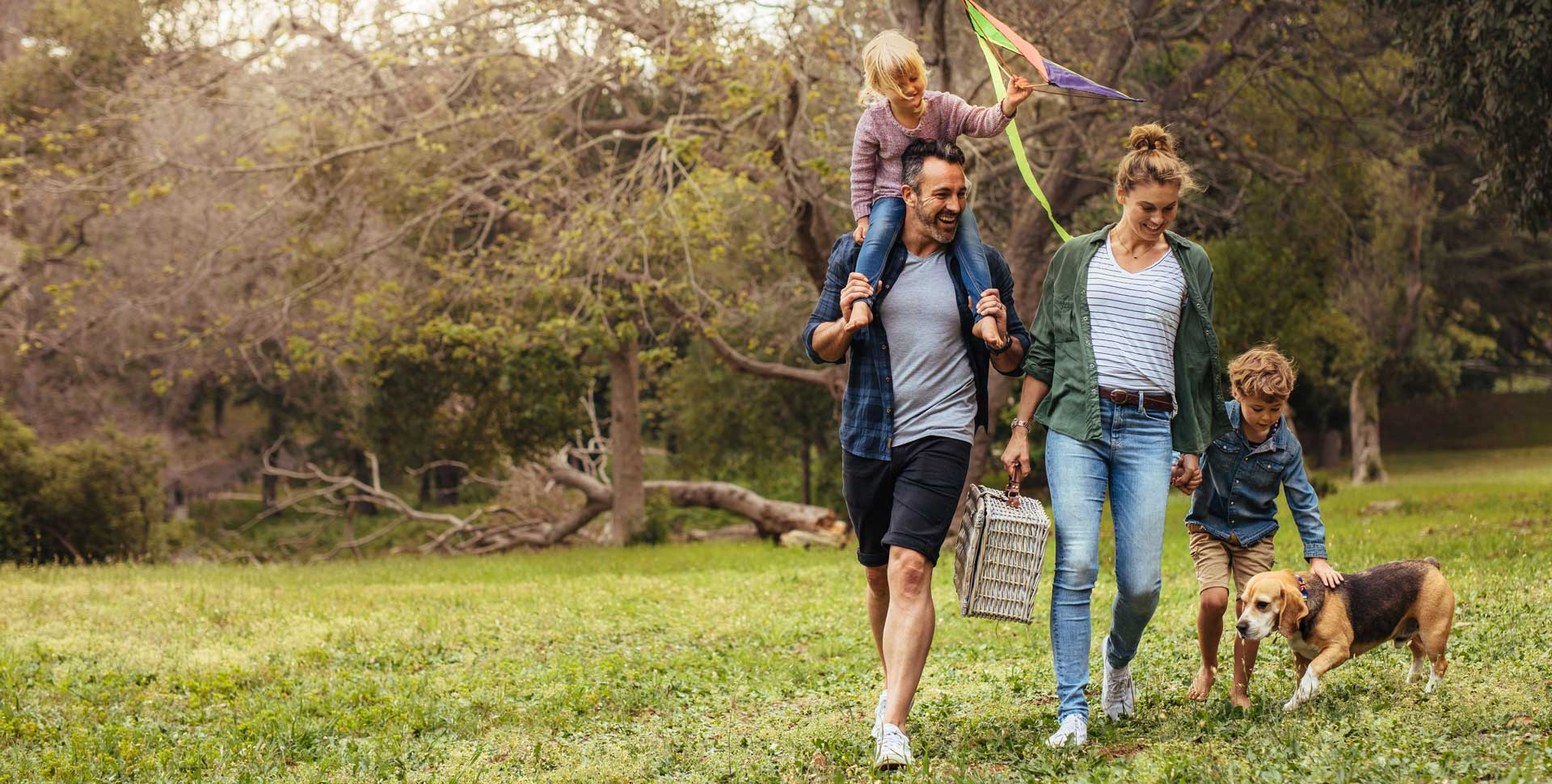 Family walking in meadow with dog and picnic basket